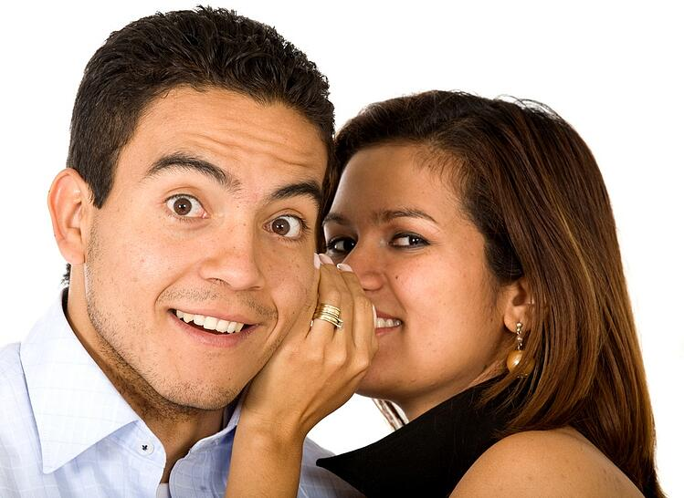 Business woman telling a businessman a secret - surprise and fun faces - over a white background.jpeg
