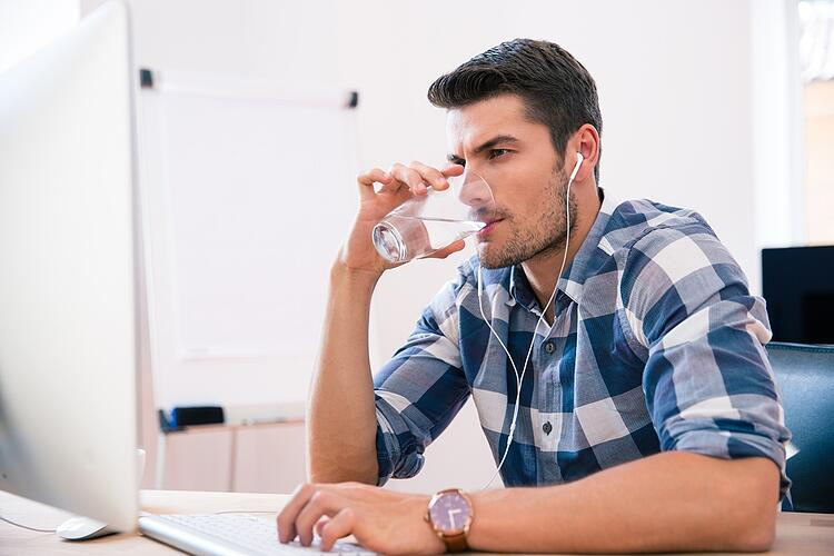 Handsome businessman in casual cloth using PC and drinking water in office.jpeg