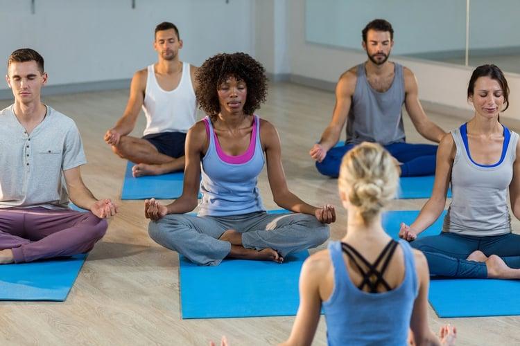 Instructor taking yoga class in fitness studio.jpeg