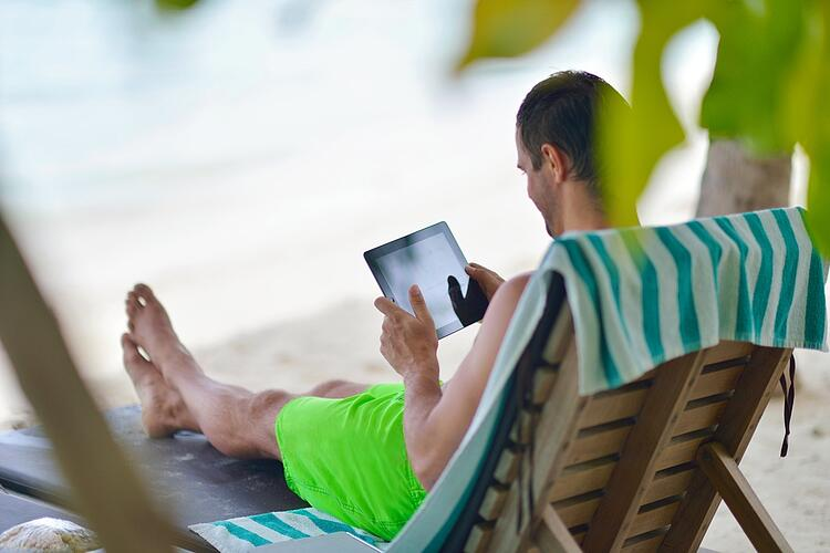business man relaxing and use tablet computer at beautiful tropical beach.jpeg