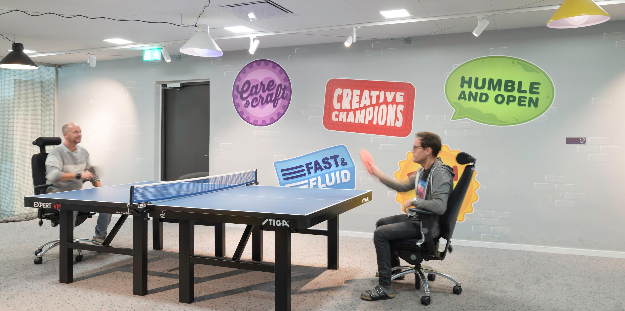 king games two people playing pingpong at work sitting in office chairs relaxing on a break
